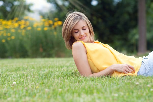 Beautiful young attractive woman, lying on the grass in park
